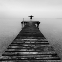 Woman standing at the end of a pier on a cloudy winter day