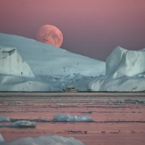HUGE MOON PEEKING FROM BEHIND A LARGE ICEBERD IN ILULISSAT FJORD, GREENLAND